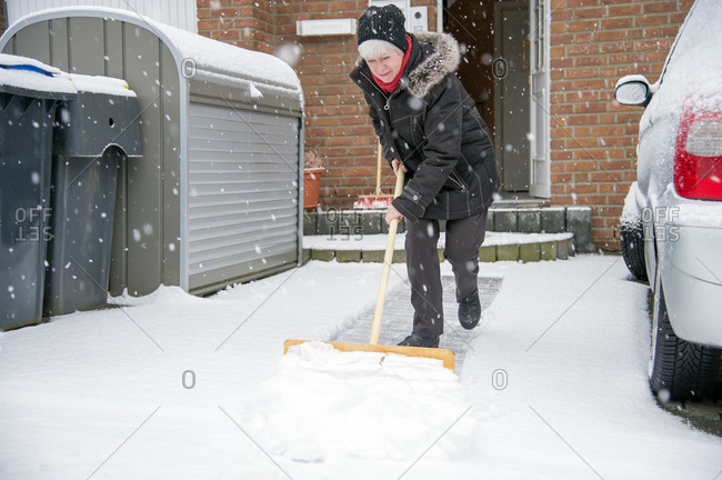 Woman shoveling snow in front of house