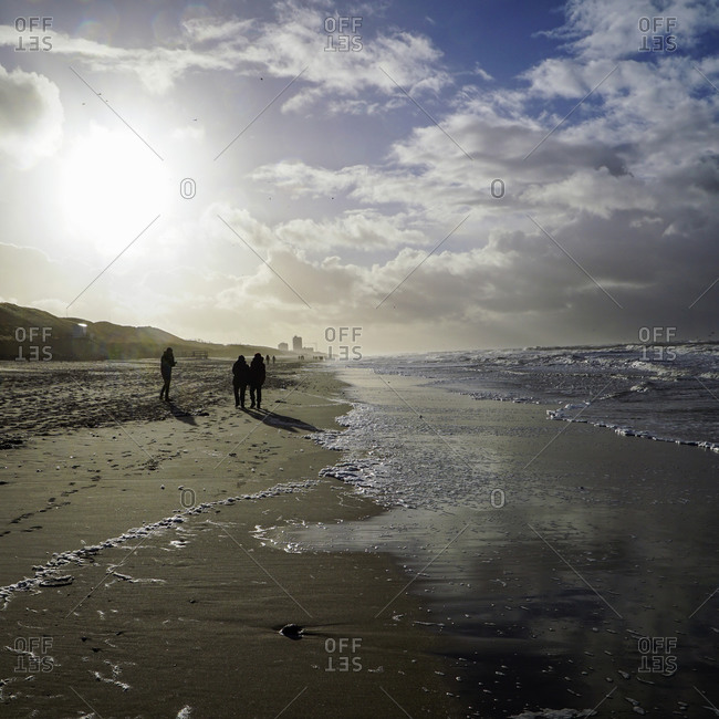 Walkers on the beach in winter at low tide