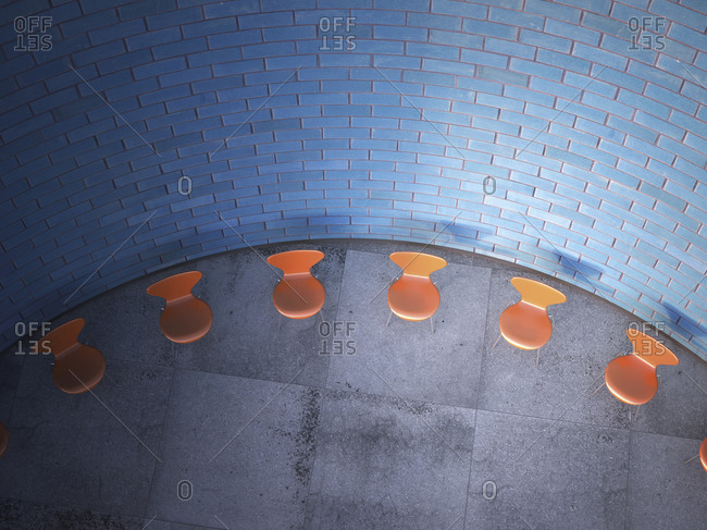 Chairs arranged in a circle in front of brick wall