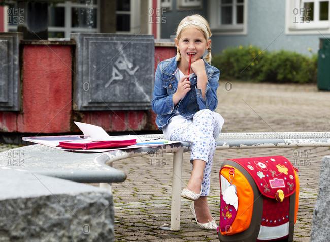 Little girl doing homework at school yard