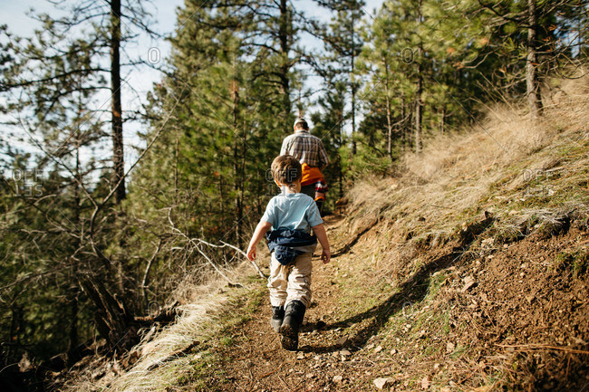 Young boy hiking with his father