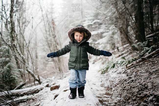 Young boy standing on a snowy plank in a forest