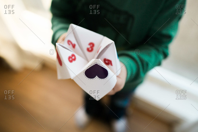 Child holding a paper fortune teller