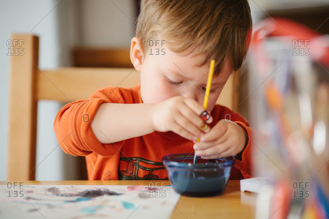 Young boy painting at a table