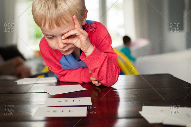 Young boy staring at flash cards on a table