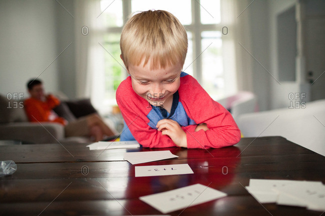 Blond boy studying with flash cards at a table