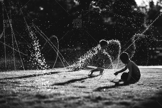 Young boys playing with a sprinkler