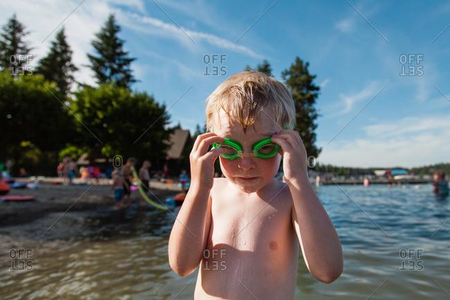 Young boy wearing swimming goggles at a lake