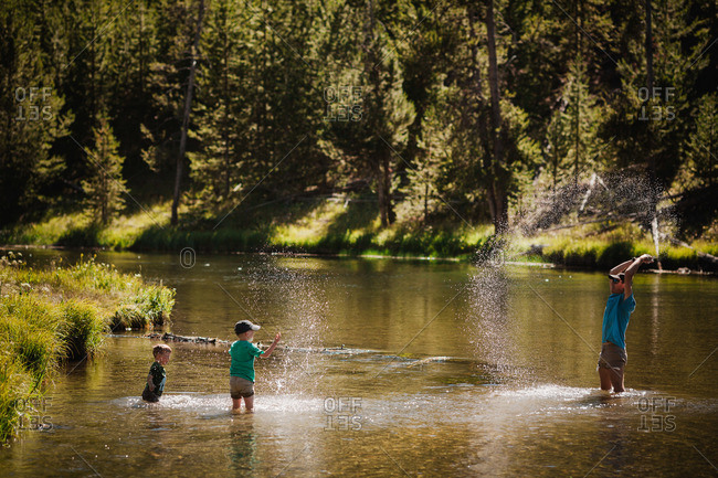 Father playing with his sons in the Firehole river in Wyoming, USA