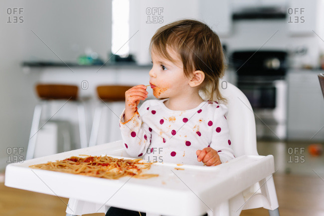 Messy toddler enjoying pasta from her high chair tray