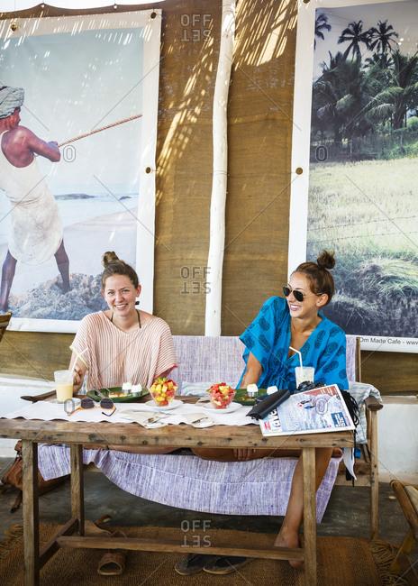 Anjuna, India - April 4, 2013: Two female tourists sitting in a café