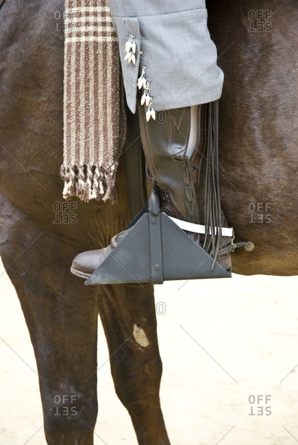 A close up of a Spanish Cowboy sitting on his brown horse and wearing brown boots and grey trousers during the Jerez Horse festival in Spain 14/05/2008.