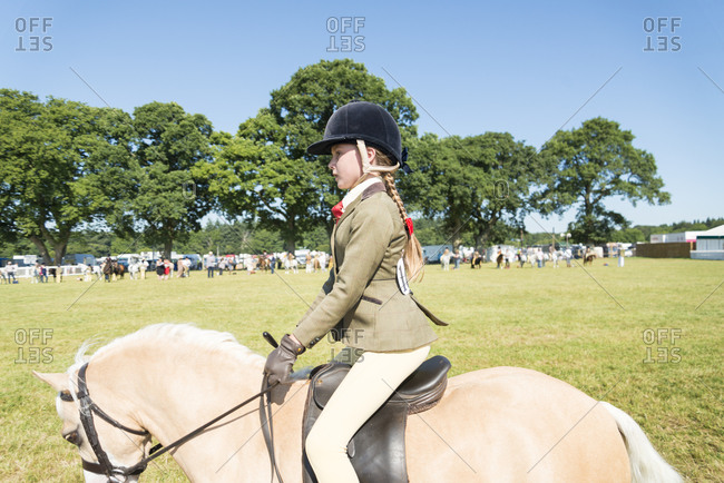 Hampshire, England, UK - July 31, 2013: Young girl riding horse in equestrian event in Hampshire, UK