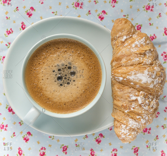 Frothy coffee in cup and croissant on a floral table cloth