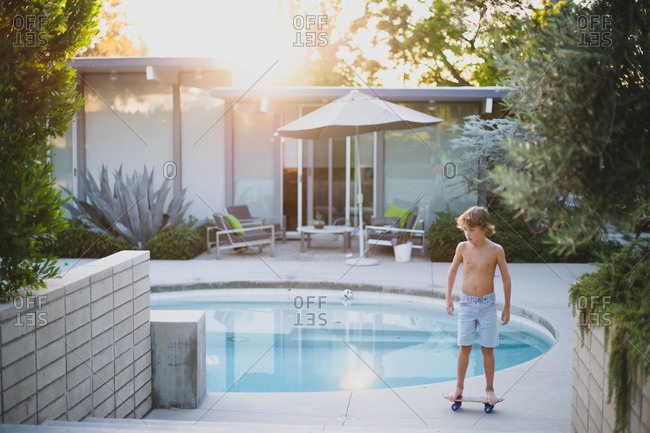 Shirtless boy standing on a skateboard in yard