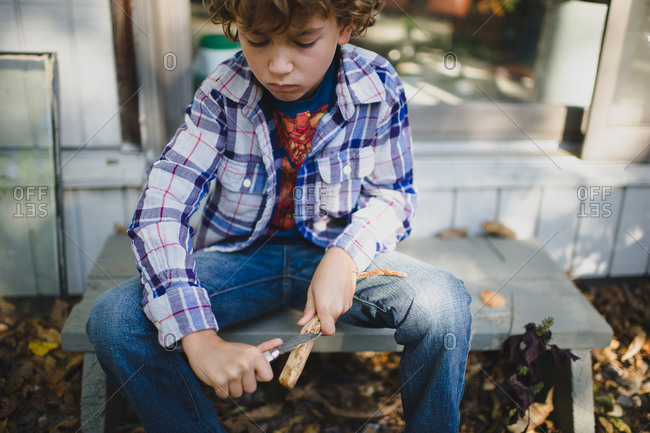 Boy sitting outside whittling a stick