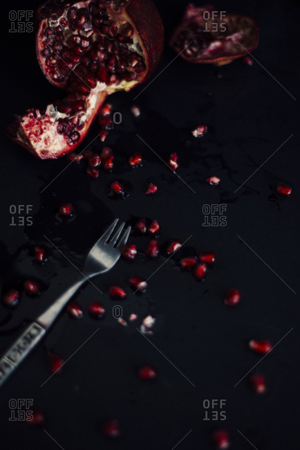 Fork by torn up pomegranate