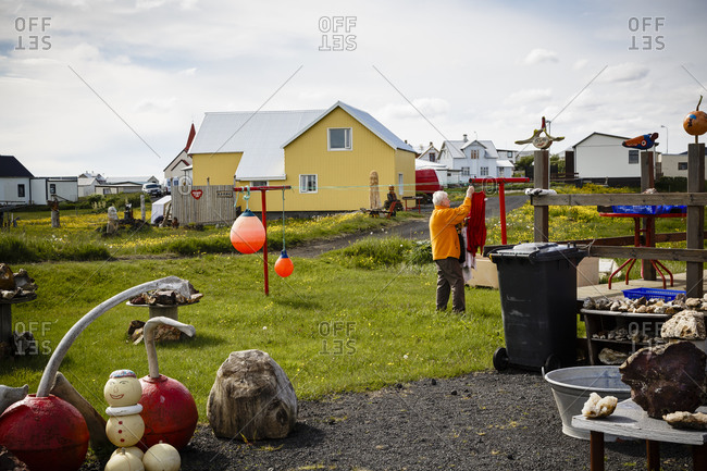 Grindavik, Iceland - June 11, 2014: An old woman hanging laundry at her house