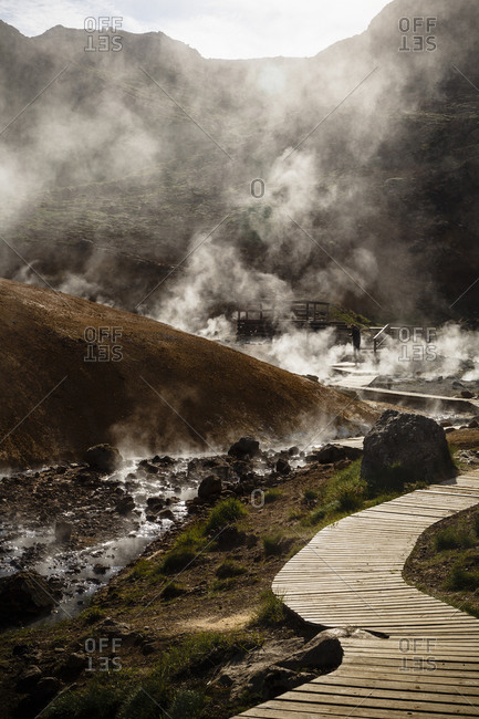 A man walks down a trail through geothermal fields at Krysuvik, Reykjanes Peninsula, Iceland