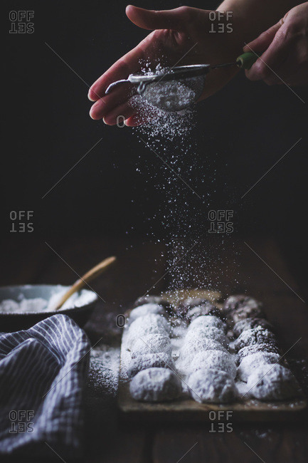 Person sifting icing sugar over gluten-free cocoa polvorones