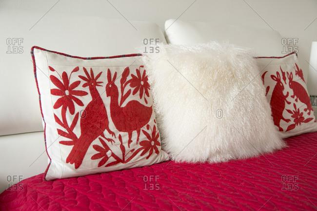 Scandinavian style folk art pillows on a bed