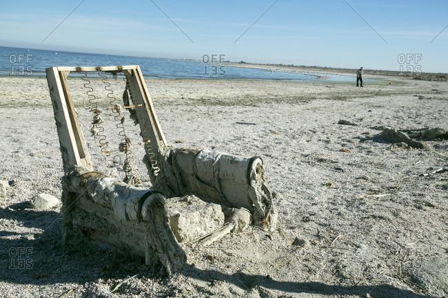 Salton Sea, California, USA - February 3, 2015: Decaying chair on the beach