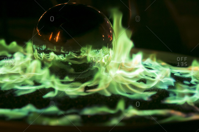 Glass ball and blue flames in a modern fireplace