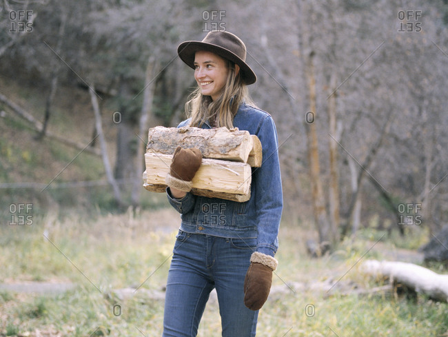 Young woman carrying firewood - Offset