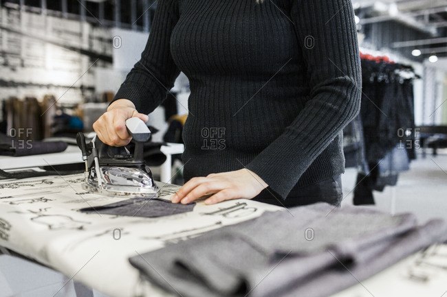 Woman in sewing studio pressing denim pieces