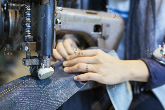 Hands of woman sewing denim with industrial machine stock