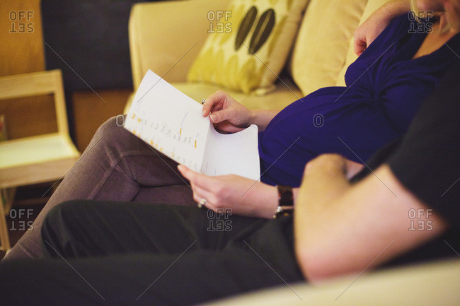 Expectant couple sitting together on a sofa