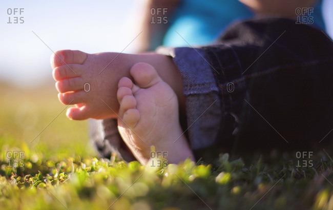 Little crossed feet of a baby sitting in the grass
