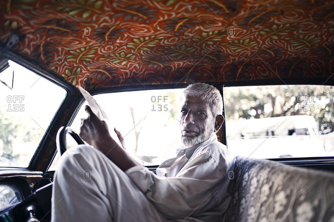 Mumbai, India - February 8, 2015: Taxi driver reading a newspaper in a car