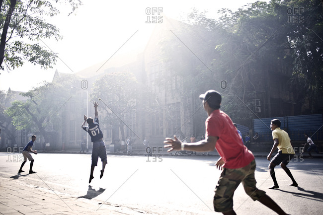 Mumbai, India - February 8, 2015: Boys playing cricket on a sunny street