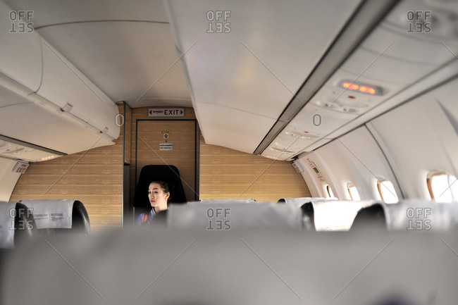 Paksong, Laos - December 14, 2014: Young female airline attendant sitting in jump seat