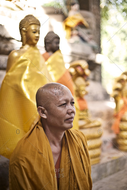 Siem Reap, Cambodia - December 19, 2014: Buddhist monk sitting next to a Buddha statue