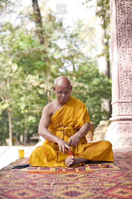 Siem Reap, Cambodia - December 19, 2014: Buddhist monk weaving bracelets