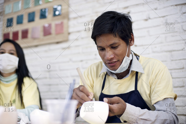 Siem Reap, Cambodia - December 20, 2014: Young man engraving a cup