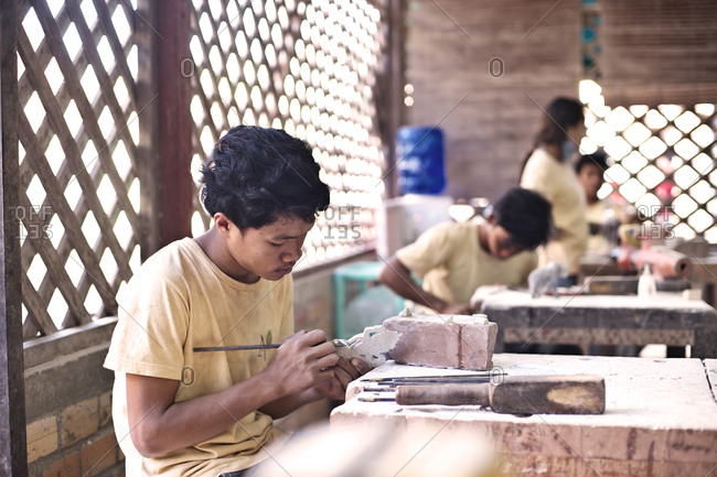 Siem Reap, Cambodia - December 20, 2014: Young man making a stone figurine