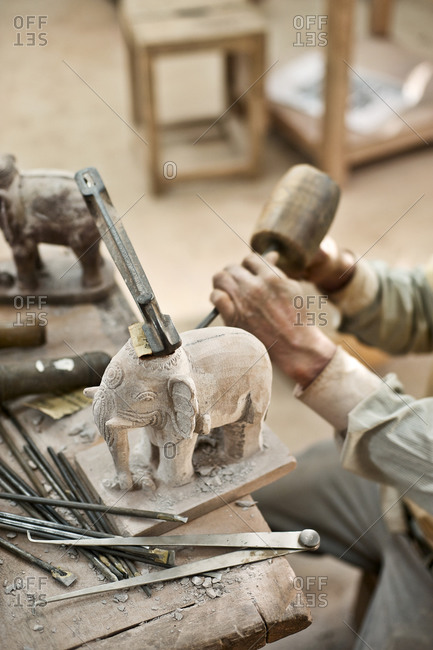 Young man carving a stone elephant