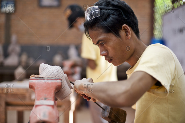 Siem Reap, Cambodia - December 20, 2014: Young man carving a Buddha head in a workshop
