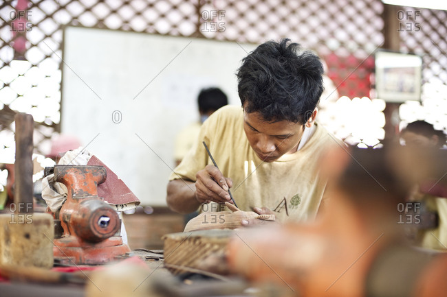 Siem Reap, Cambodia - December 20, 2014: Young man carving a statuette in a workshop