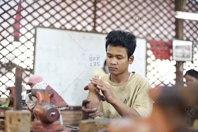 Siem Reap, Cambodia - December 20, 2014: Young man carving a wooden elephant