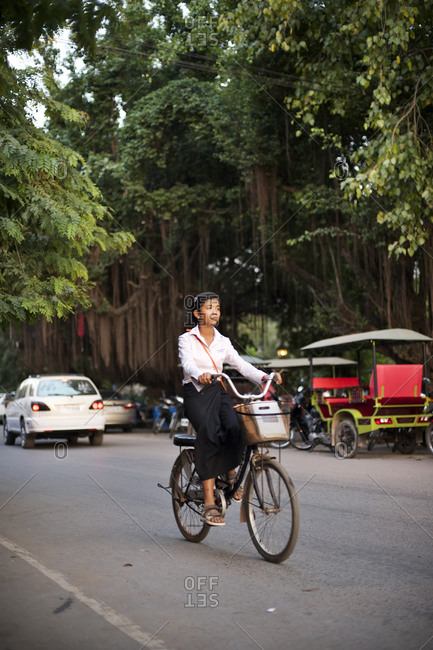 Siem Reap, Cambodia - December 20, 2014: Woman riding a bicycle on a road