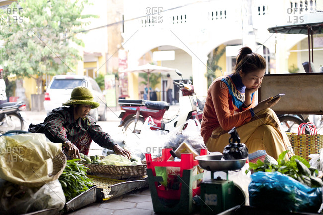 Siem Reap, Cambodia - December 21, 2014: Young woman using a smartphone at a market