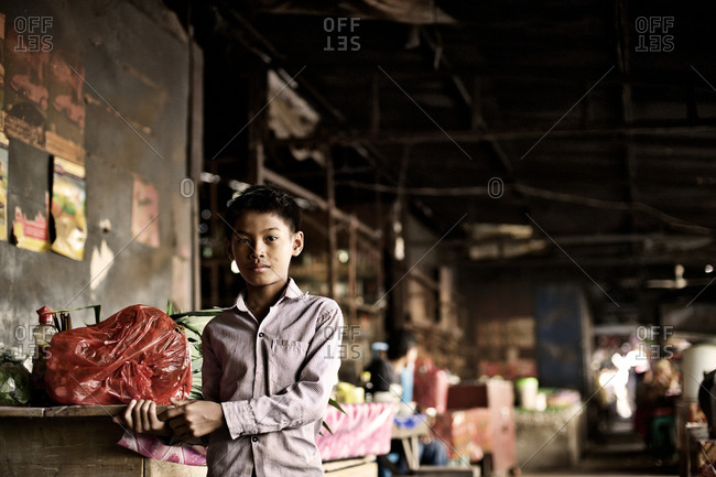 Siem Reap, Cambodia - December 21, 2014: Young boy standing at a market
