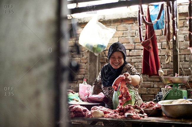 Siem Reap, Cambodia - December 21, 2014: Woman arranging meat at a market