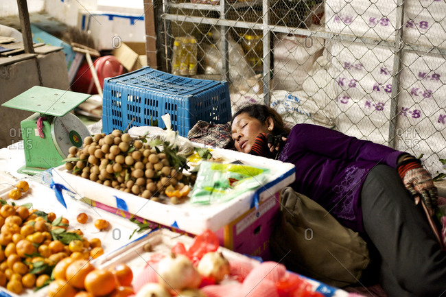 Siem Reap, Cambodia - December 21, 2014: Vendor sleeping at a market