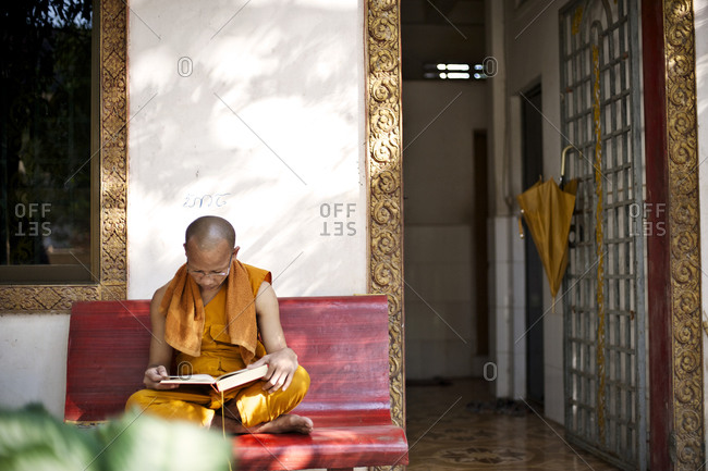 Siem Reap, Cambodia - December 22, 2014: Buddhist monk reading on a bench