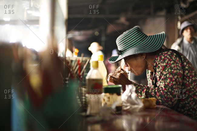 Siem Reap, Cambodia - December 22, 2014: Woman eating noodles